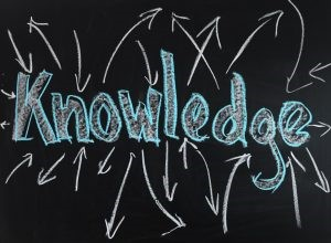 the word knowledge is written in blue and white chalk on a black background with white arrows going in different directions