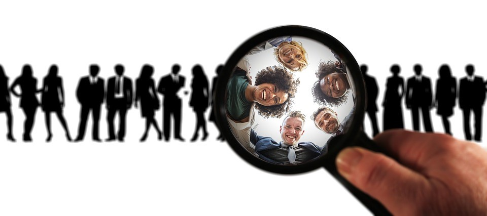 a row of people in silhouette with five people illuminated by a magnifying glass