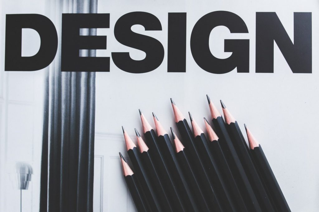 """the word """"design"""" in black letters with some sharpened pencils underneath"""