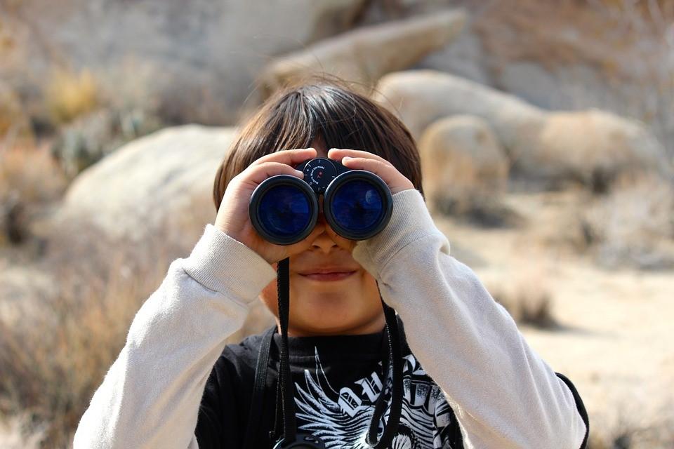 young boy peering through binoculars in a desert