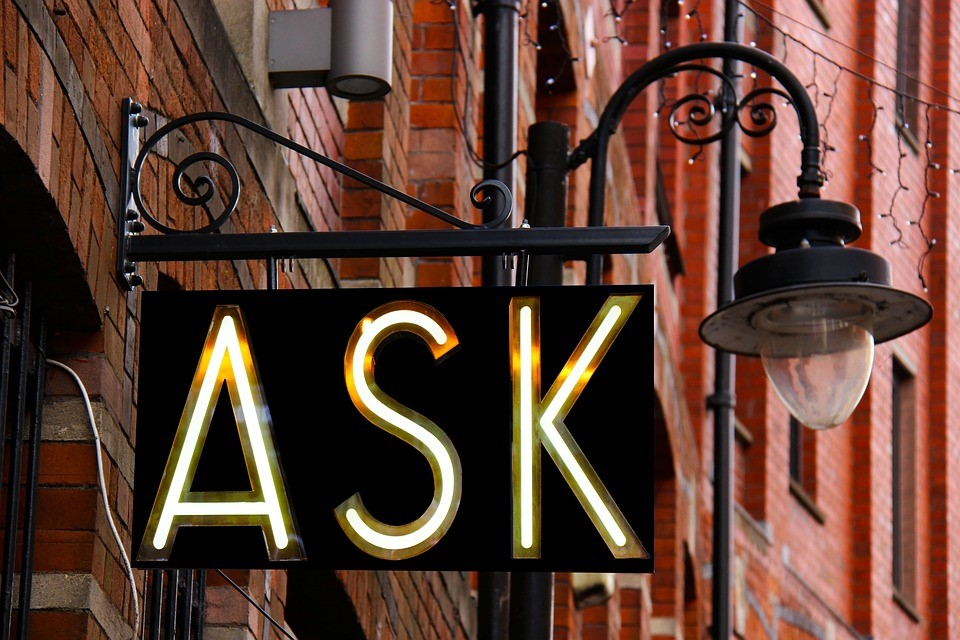 """an illuminated street sign that reads """"ask"""""""