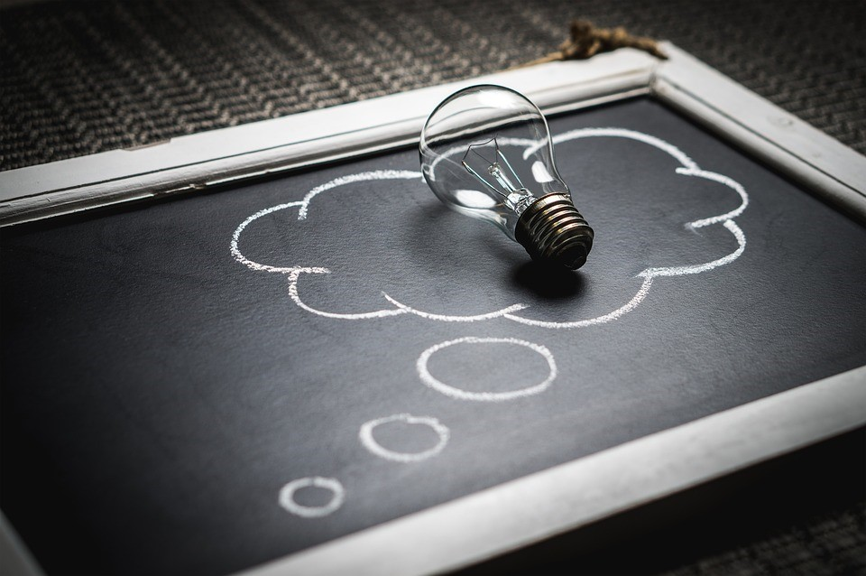 a lightbulb inside of a thought bubble on a chalkboard