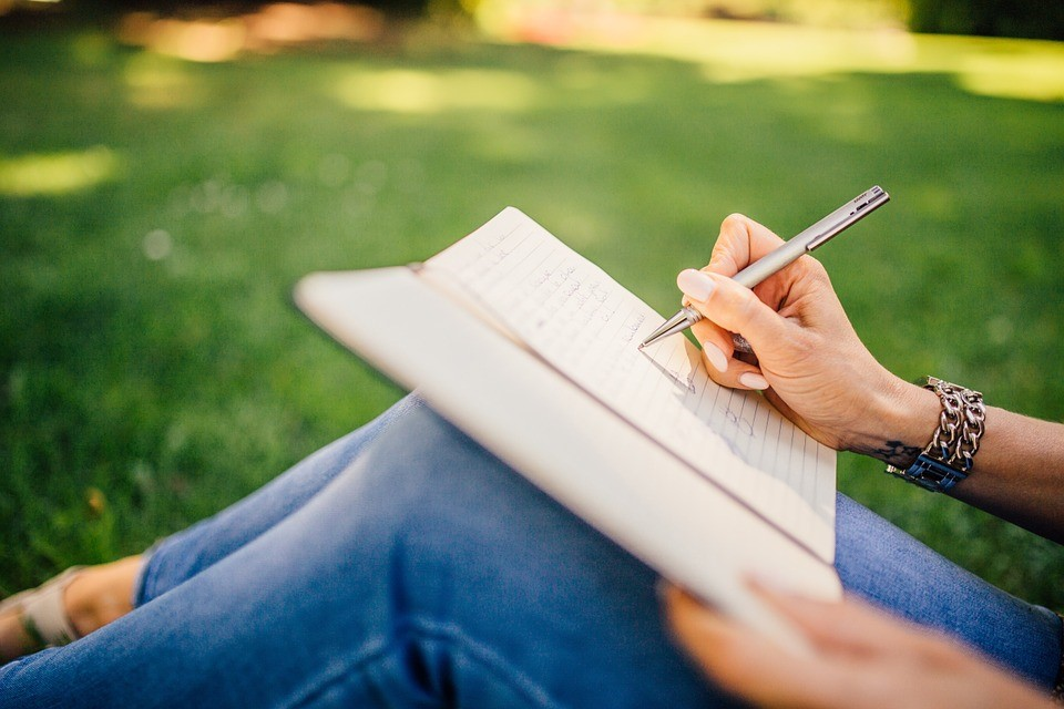 a woman writing down notes in a journal while seated in a field