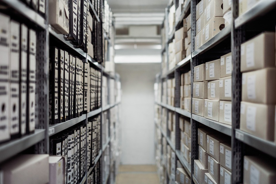 stacks in a library, showing books on one side and boxes on another