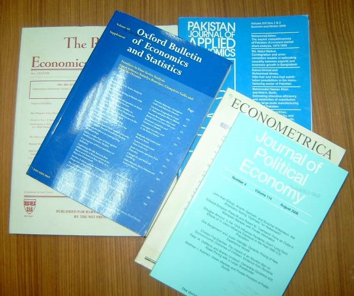 print editions of journals in the economics discipline on a desk stacked on a desk
