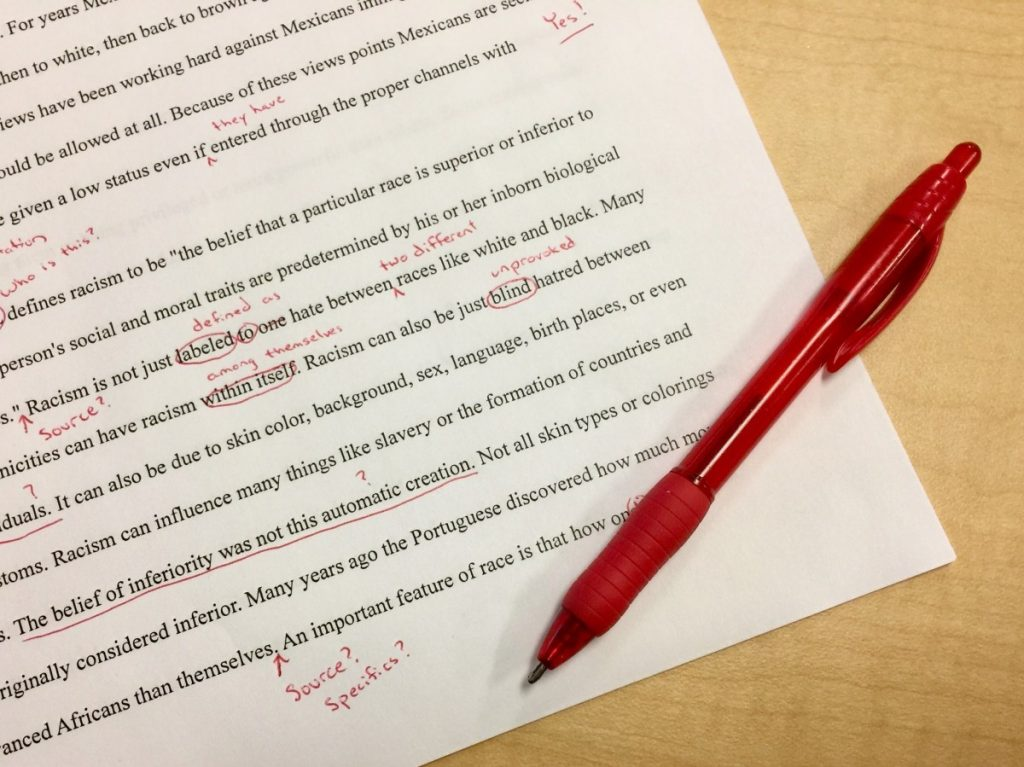 a typewritten paper with corrections in red ink written on it