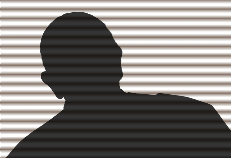 a person in silhouette behind blinds