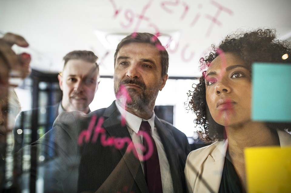 three people writing on a clear board with post-it notes, planning something