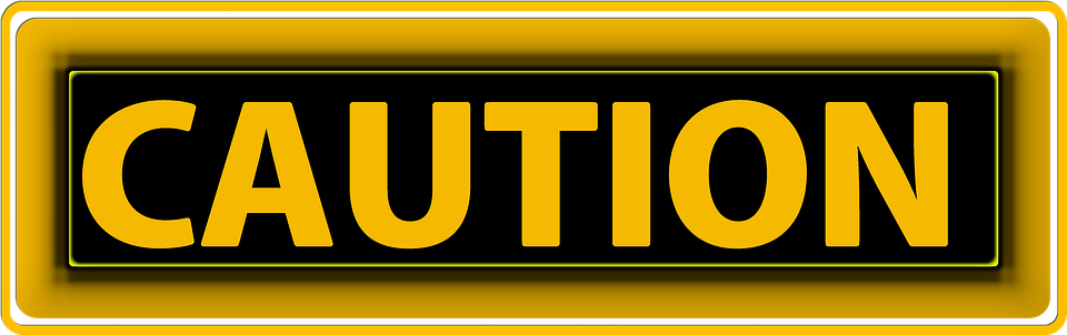 yellow sign reading caution