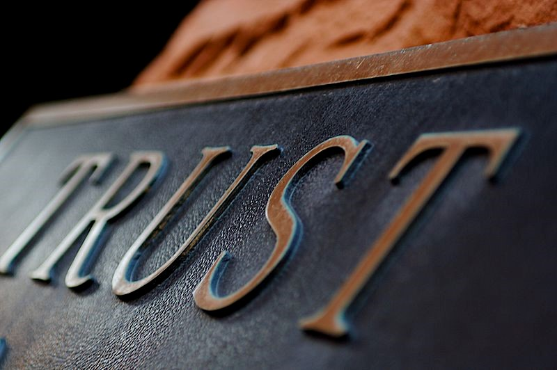 a metal sign with the word trust on it