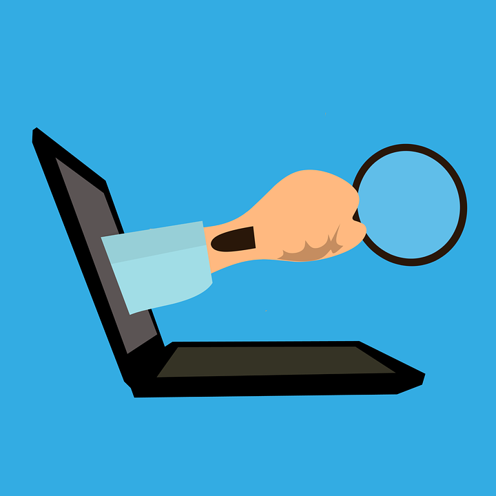 laptop with an arm holding a magnifying glass coming out of it