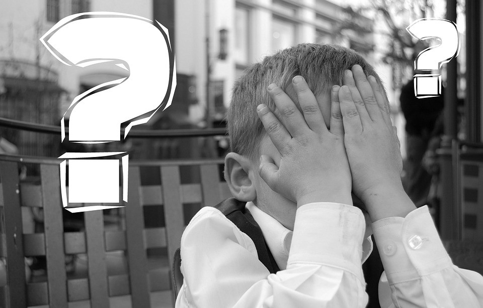 child with hands over his face in embarrassment with a question mark next to him