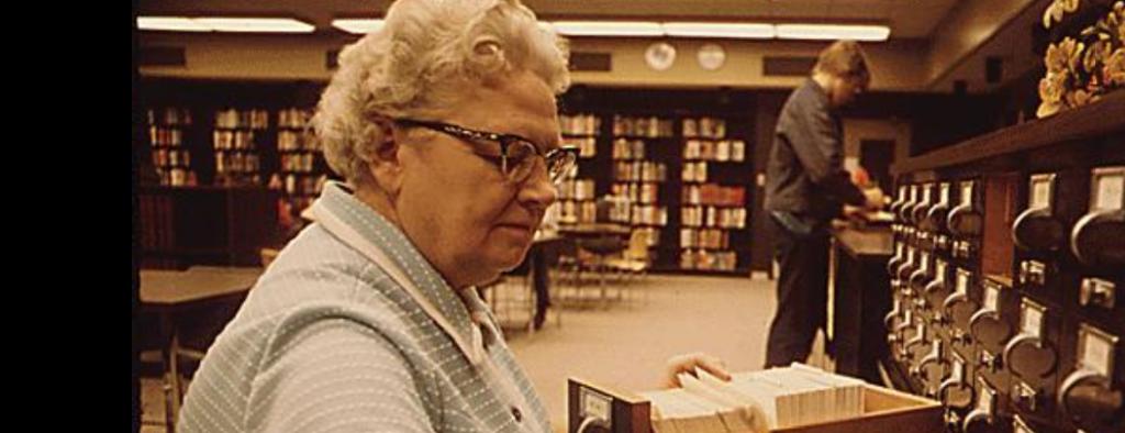 older female librarian sorting a cart catalog