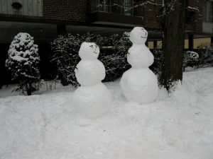 Two snowpeople are shown, each constructed of three round balls of snow