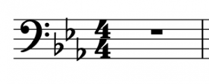 A bass clef is shown on a staff, followed by a three-flat key signature, and a 4/4 time signature.