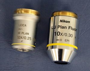 Figure 2.4.12 Objective lenses from two brands of polarizing light microscope. The magnification (10x) and numeric aperture (0.25 and 0.30) are written on each objective.