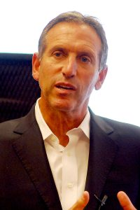 A photograph of Howard Schultz from the navel up. He is wearing a white collared shirt without a tie and a suit jacket.