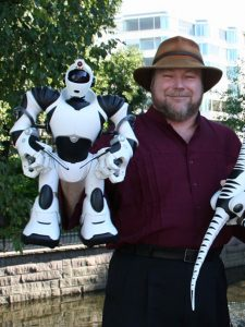 A photograph of Mark Tilden wearing a wide brimmed hat, holding a white Robosapien, an approximately one foot high humanoid robot, in one hand. He is standing outside with an office building in the background.