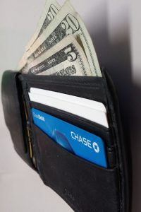 A photograph of an open wallet from the side. Two twenty dollar bills and a five dollar bill stick out of the wallet stacked on top of each other. Two white cards and a Chase card are in the visible.