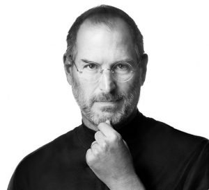Black and white photo of Steve Jobs wearing characteristic black turtleneck and pinching his chin between forefinger and thumb