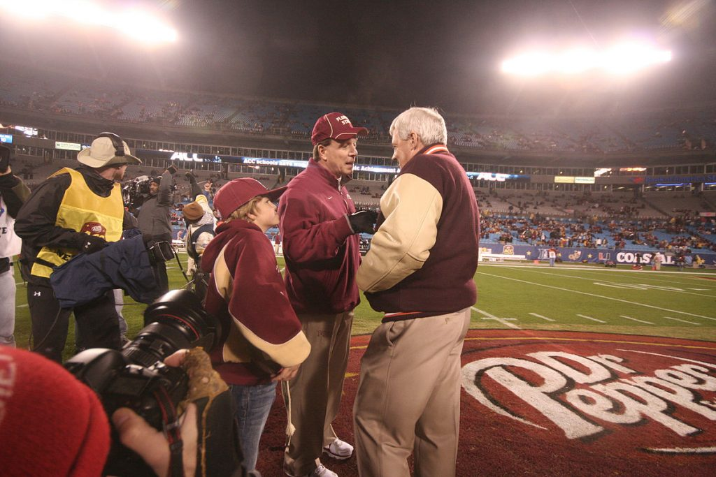 Frank Beamer stands to the right of Jimbo Fisher on a football field in a stadium with people in the stands at night.