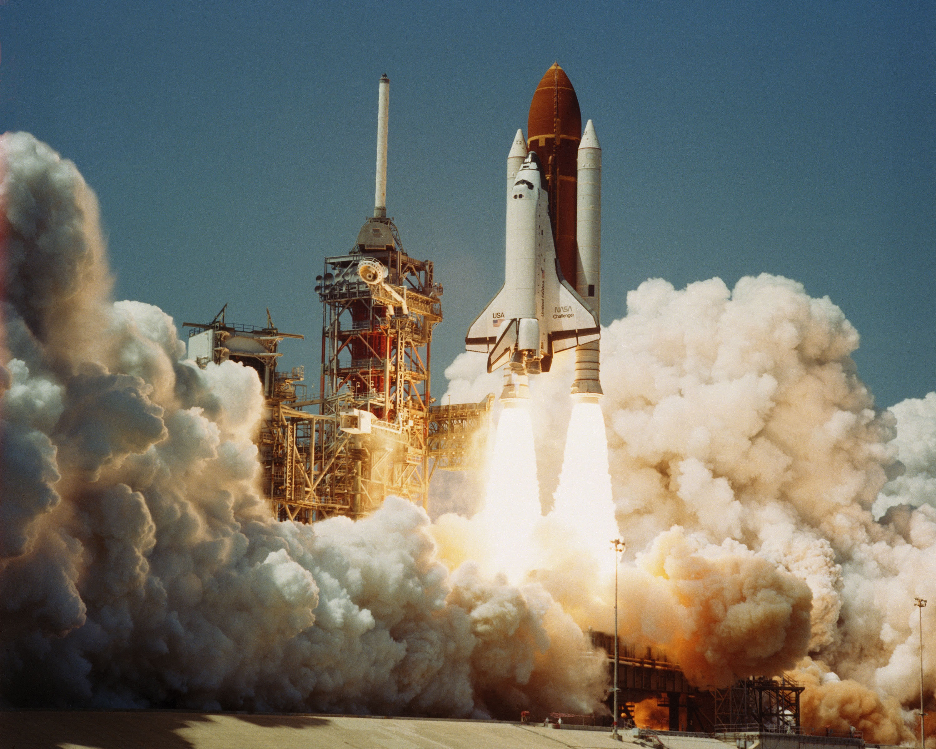 A space shuttle, the Challenger, in take off, showing flames exiting rockets and surrounded by billowing clouds created by smoke. Space Transportation System Number 6, Orbiter Challenger, lifts off from Pad 39A carrying astronauts Paul J. Weitz, Koral J. Bobko, Donald H. Peterson and Dr. Story Musgrave.