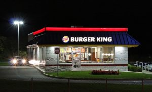 A photograph of a Burger King at night, as seen from a road. The building is lit up with lights on it, and a streetlight is in the background. A car is at the drive thru window with its headlights on.