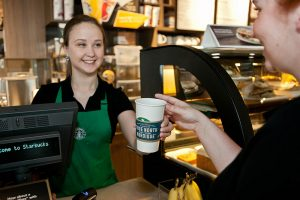 A photograph of a Starbucks barista behind a counter in Starbucks, serving a coffee to a customer while smiling.