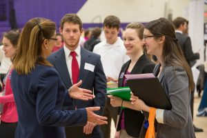 A photograph of a recruiter talking to three students at a college campus job fair. They are all dressed in business professional clothing.