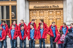 Two lines of 13 male models, wearing the same outfit: jeans, a blue button down shirt, and a red sweater. They are standing in front of the doors of an Abercrombie and Fitch store.