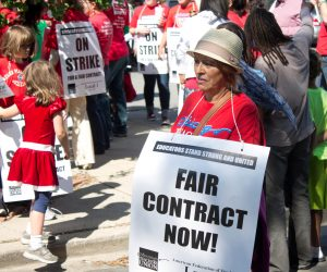 """A photograph of a teacher protesting in a crowd, with a large, square sign around her neck reading """"Fair Contract Now!"""""""