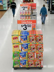 """A sale display in a Wal-Mart aisle. The display shows four different types of cereal stacked beside each other, with a price sign that reads """"$3.50"""" sitting on top. In the background are other sales displays and several customers walking in the aisle."""
