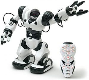 A photograph of a Robosapien, similar to the one pictured in figure 14.1, on a white background. The robot is standing, looking to the right, and holding its arm up toward the right corner. Beside the robot is a black and white remote, smaller than the Robosapien, sitting upright.