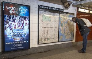 """A photograph of a wall in a subway in New York. The left side of the wall features a vertical, rectangular television screen showing an advertisement for NCAA March Madness. The right side of the wall features a large bulletin board labeled """"Customer Information Center,"""" showing two different maps. A person with a backpack is to the right of the bulletin board, bent over reading the map."""