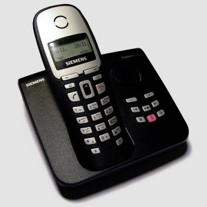 A photograph of a cordless landline phone sitting on the left side of its dock, on a white background. The phone brand is Siemens. The phone dial buttons are on the phone apparatus, with additional buttons on the dock to the right.