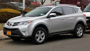 A photograph of a silver RAV-4, shown from the side. It is parallel parked on a street, with another car behind it and bushes in the background.