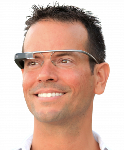 A photograph of a person wearing Google Glass, a pair of silver glasses with a small black camera on the right side. The person is looking off into the distance to the left in front of a white background.