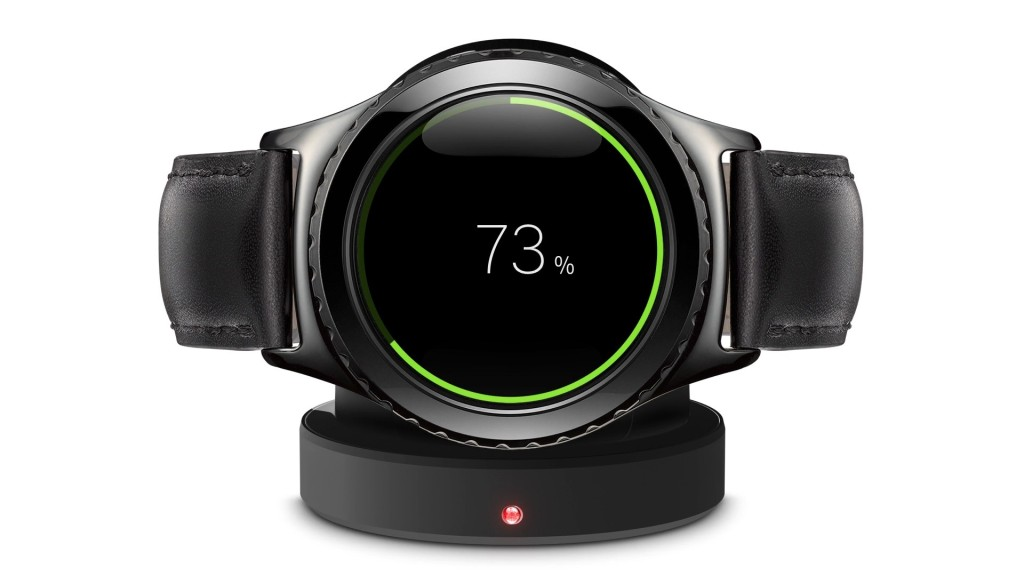 A photograph of a Samsung smart watch, sitting on its charger on a white background. The watch has a round face, and the face and band are black. A green ring around the face shows the charging percentage. The Percentage is displayed on the face, 73%. The charger has a red light in the middle.