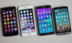 A photograph of four different smartphones, laying side by side on a white background, each displaying their respective homepages.