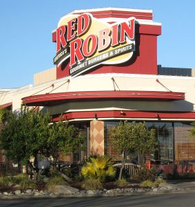 A photograph of the outside of a Red Robin restaurant, as seen from the road. The Red Robin sign sits on top of the building, and shrubs sit in front of the building.