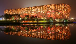 A photograph of the Beijing National Stadium at night, taken from across water. The National Stadium is lit up by yellow lights from within. A reflection of the stadium appears on the water.