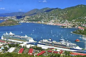 A photograph of two cruise ships docked in a bay, Charlotte Amalie, in the Virgin Islands. On land beside the cruise ships are eight buildings with red roofs. Smaller boats are in the bay away from the cruise ships. A mountain range lies in the background.