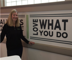 """A photograph of Amy Ankrum, standing to the left of a wall that reads """"Love What You Do"""" Where love is written sideways."""