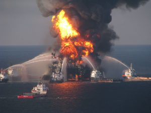 A photograph of an oil rig engulfed in flames with dark smoke billowing upward. Five boats surround the oil rig, spraying water on it to stop the fire.