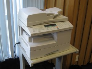 A photograph of a printer sitting on a table just slightly larger than the base of the printer.